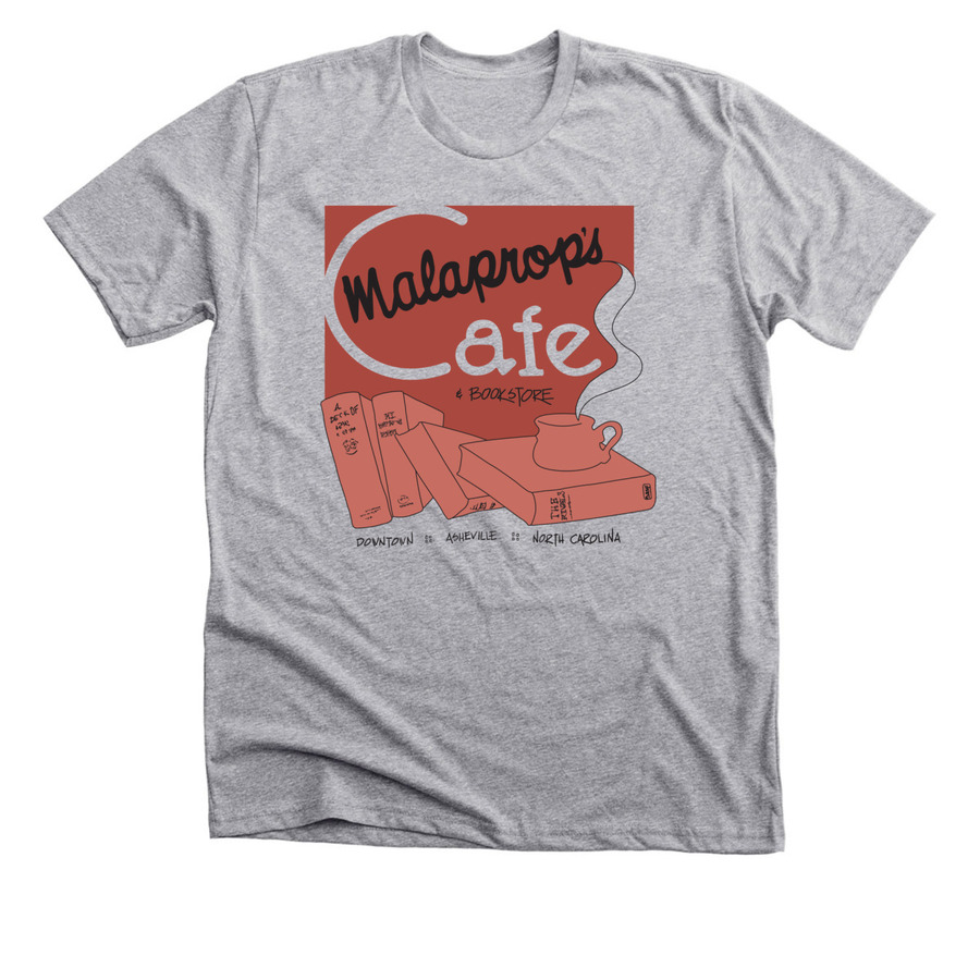 Image is of a grey tee shirt with red and orange drawing depicting a stack of books and coffee cup. Image text conveys the store name and location.